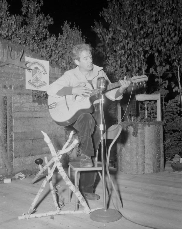 Félix Leclerc chante et joue de la guitare sur une scène décorée de bois rond