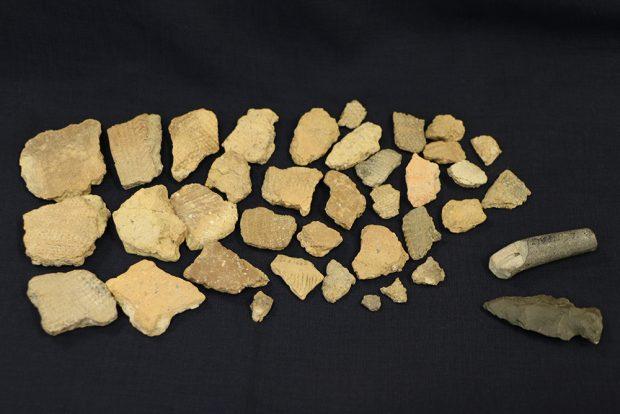 Artefacts amérindiens disposés sur un fond noir. Au bas à droite, une pointe de projectile en forme de flèche et un fragment de pipe en céramique, de couleur grise. À gauche, une vingtaine de tessons de poterie, beige et gris ornés de motifs en chevrons.