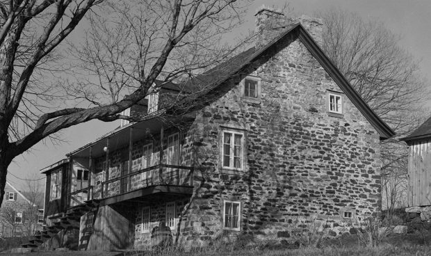 Photographie en noir et blanc d'une habitation du 18e siècle en pierre et en bois vue de côté. La maison présente des cheminées en pierre massive et une grande galerie en bois.