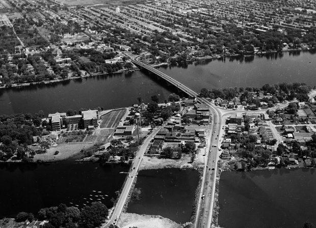 Vue aérienne en noir et blanc d'un pont qui enjambe une large rivière. Sur les deux rives, des quartiers habités.