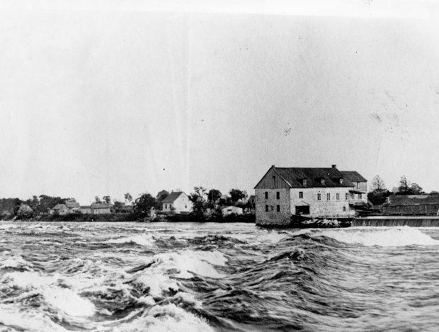 Photographie en noir et blanc d'un moulin au loin. Au premier plan, une rivière coule. Les vagues sont agitées.