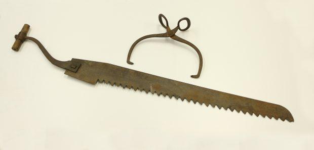 Photographie d'outils pour la coupe de glace. Sur un fond blanc, une pince en métal brun utilisée pour transporter les blocs et une scie en fer rouillé avec une poignée en bois.