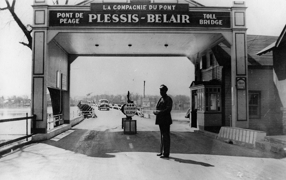 Photographie en noir et blanc de l'entrée du pont Plessis-Bélair. Une arche indique le nom du pont et la mention « pont à péage / toll bridge ». Un gardien est placé devant le poste de péage.