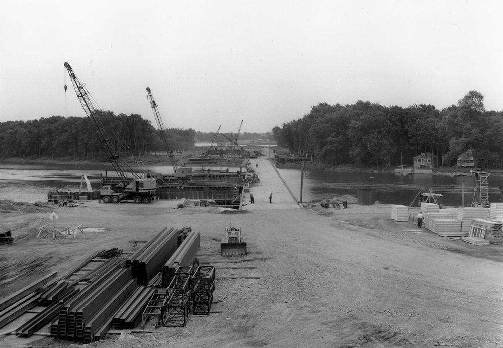 Photographie en noir et blanc de la construction de l'autoroute 15. Deux travailleurs, une grue et des matériaux de construction sont visibles, ainsi que des grosses poutres de métal et des morceaux de bois.