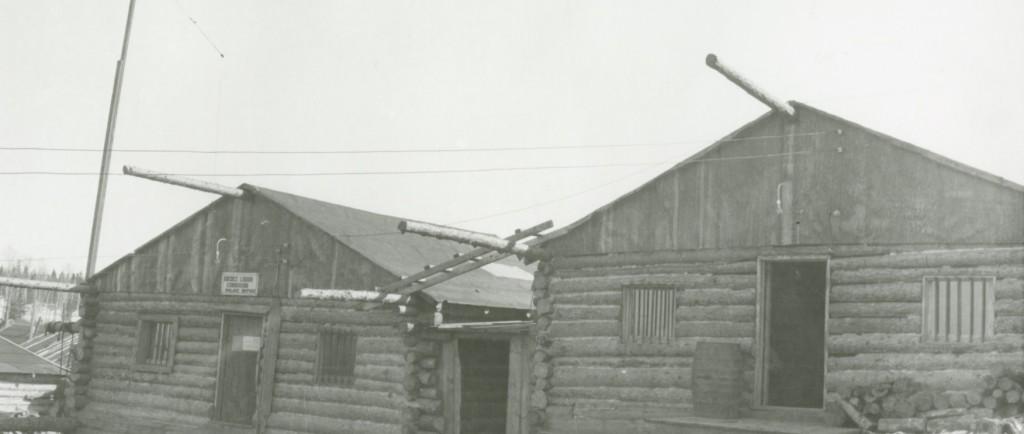Photographie en noir et blanc de deux cabanes en bois rond avec des barreaux d'installés sur les fenêtres. Une affiche est posée au-dessus de la porte du bâtiment de gauche.