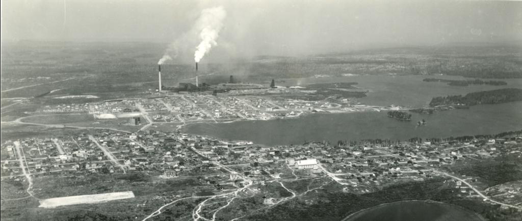 Photo noir et blanc de deux agglomérations, séparées par un terrain vague, construite autour d'un lac. À l'arrière-plan, la fonderie avec trois chevalements et deux cheminées qui fument.