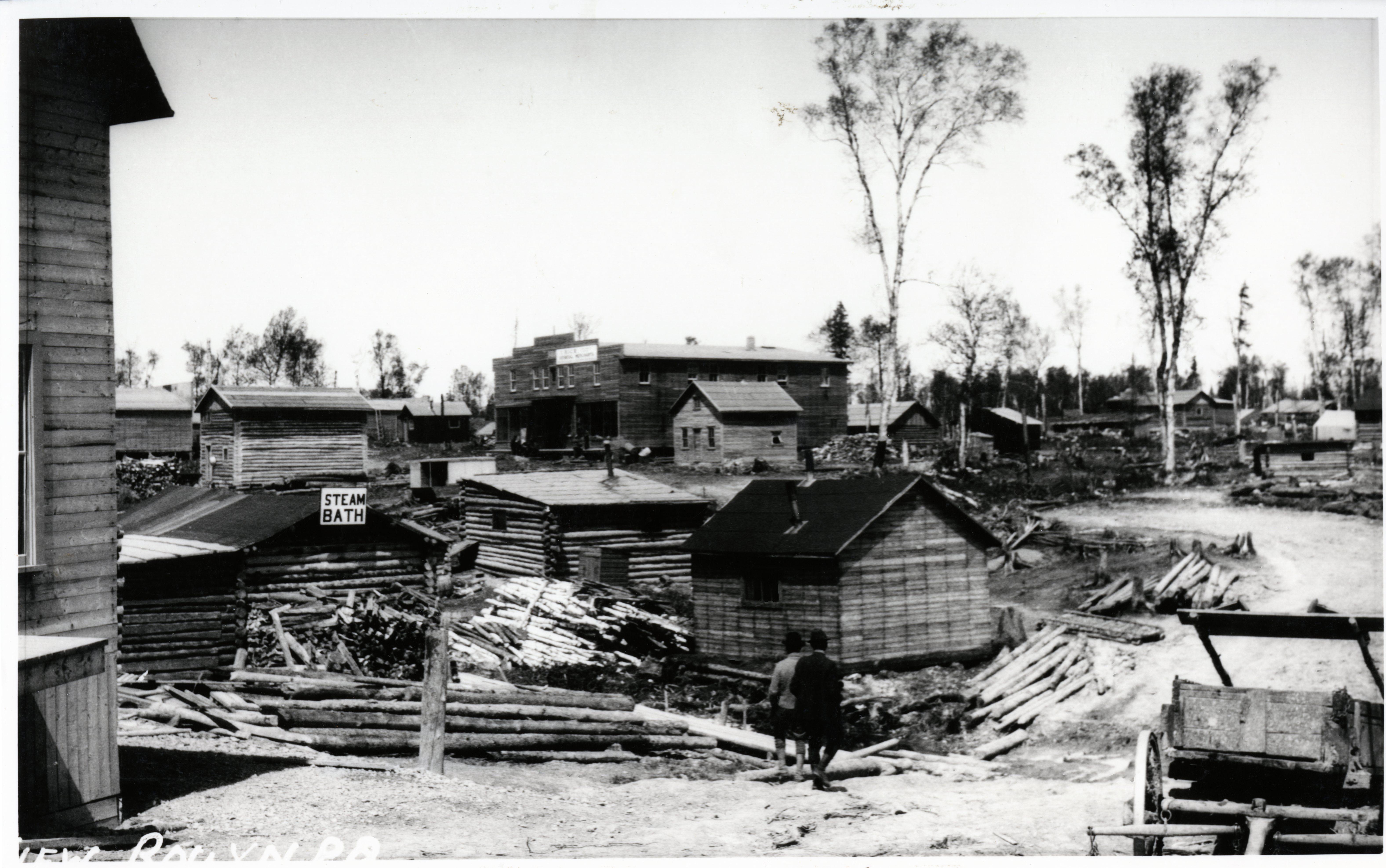 Photographie noir et blanc de plusieurs bâtiments rudimentaires, en bois rond ou en planches, dont un bain à vapeur, qui est indiqué par une affiche steam bath.