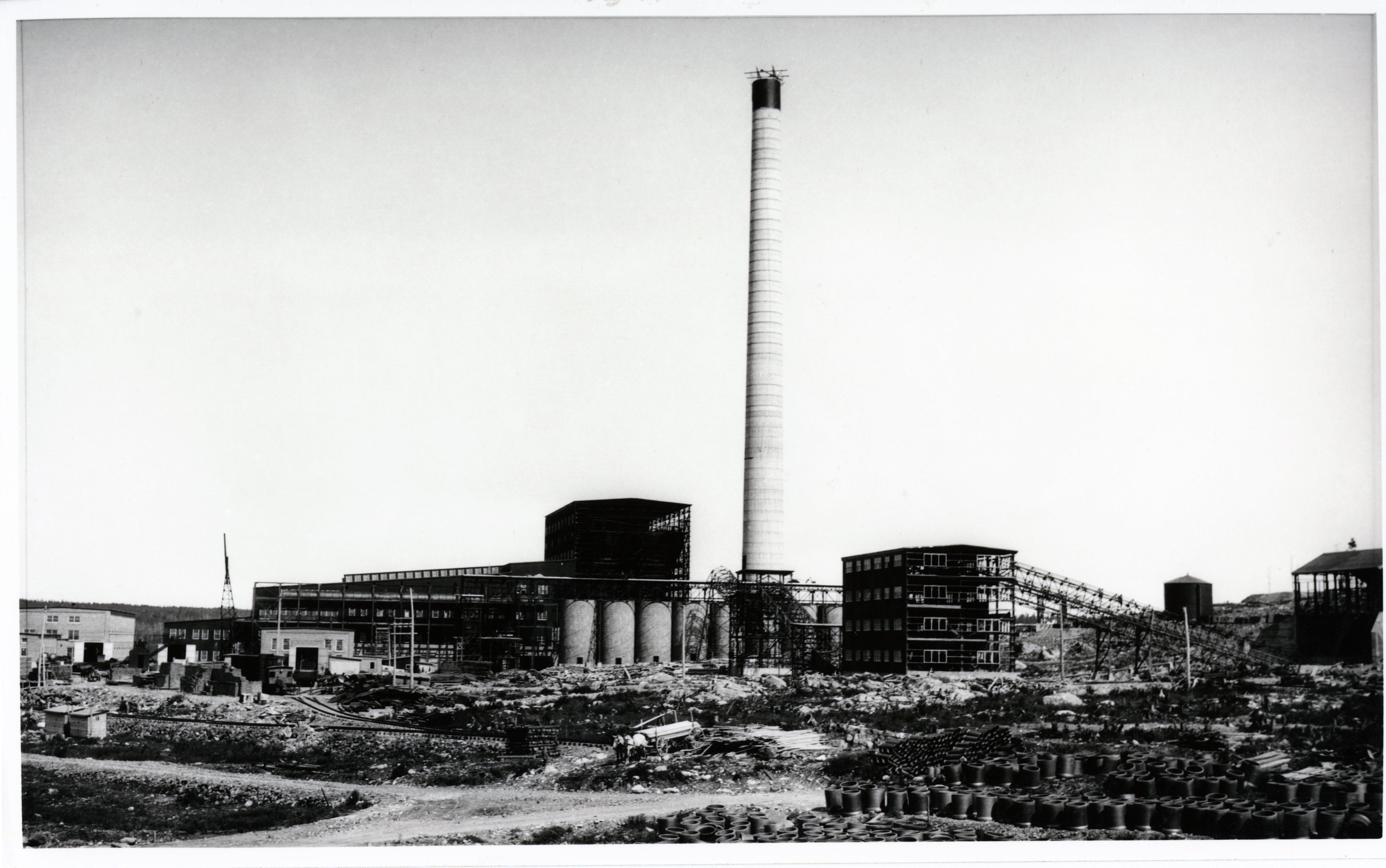 Photographie en noir et blanc de la construction de la fonderie Horne. Au centre, une cheminée et à l'avant-plan, plusieurs matériaux de construction étalés un peu partout.