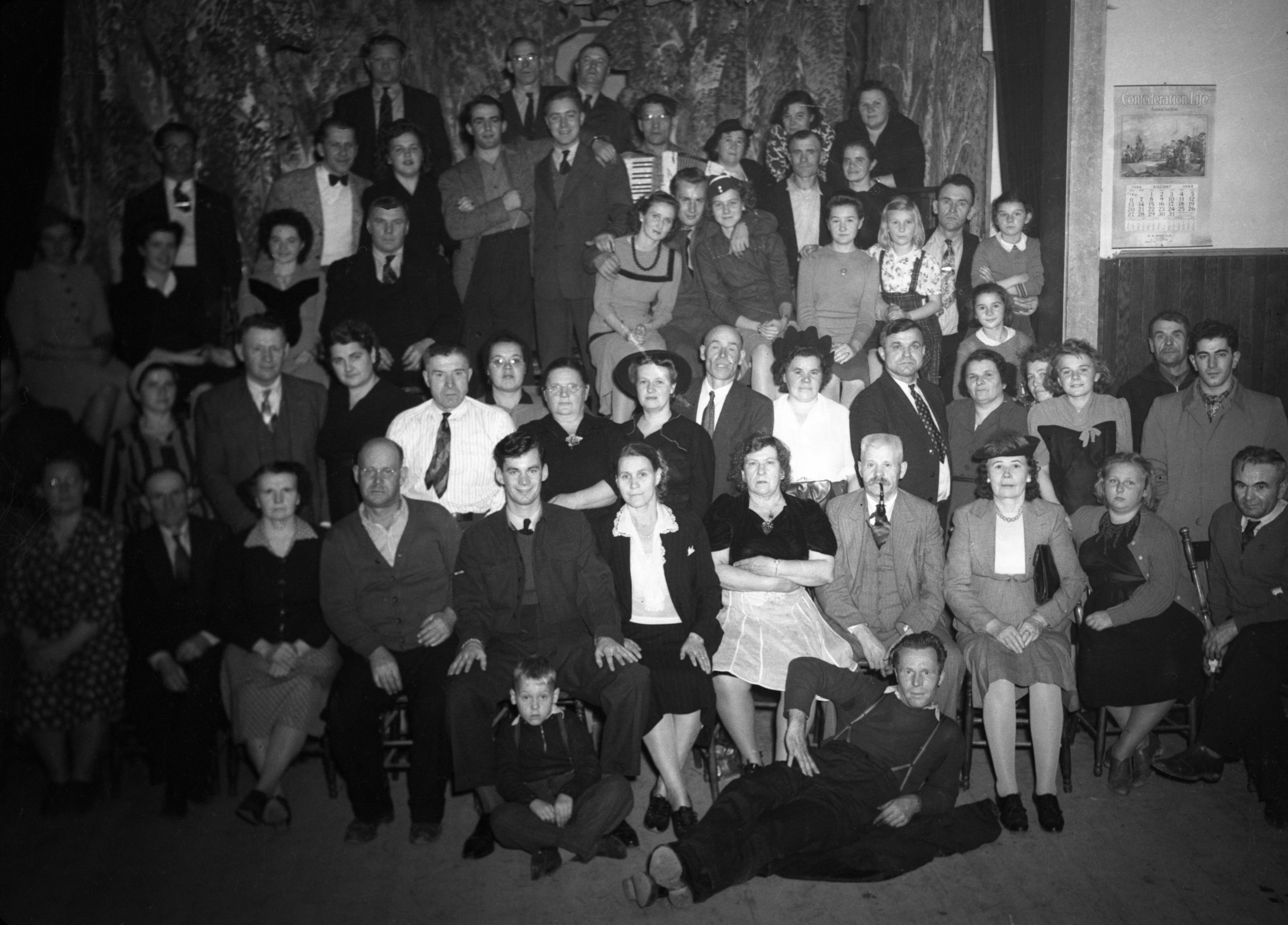 Photographie en noir et blanc d'une cinquantaine de personnes : vingt-trois femmes, vingt-quatre hommes et quelques enfants. Une des personnes tient un accordéon dans ses mains.
