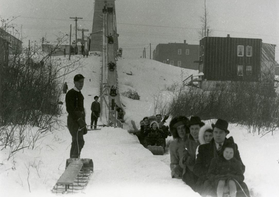 Photographie en noir et blanc de plusieurs personnes sur des traines sauvages qui glissent à partir d'une structure de bois installée sur une colline.