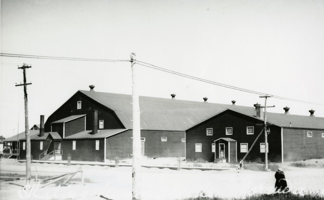 Photographie en noir et blanc de deux bâtiments, avec des toits de tôle et très peu de fenêtres. Sur le sol, une fine couche de neige.
