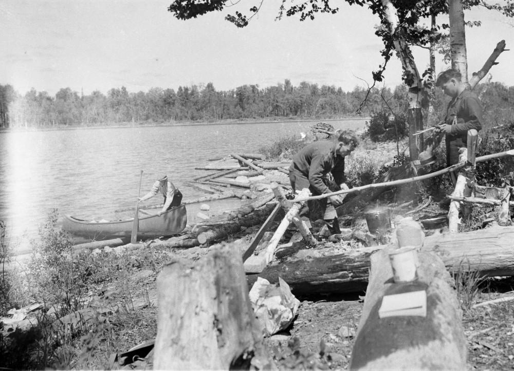 Photographie en noir et blanc de trois prospecteurs. Pendant qu'un arrive en canot, les deux autres préparent le feu.