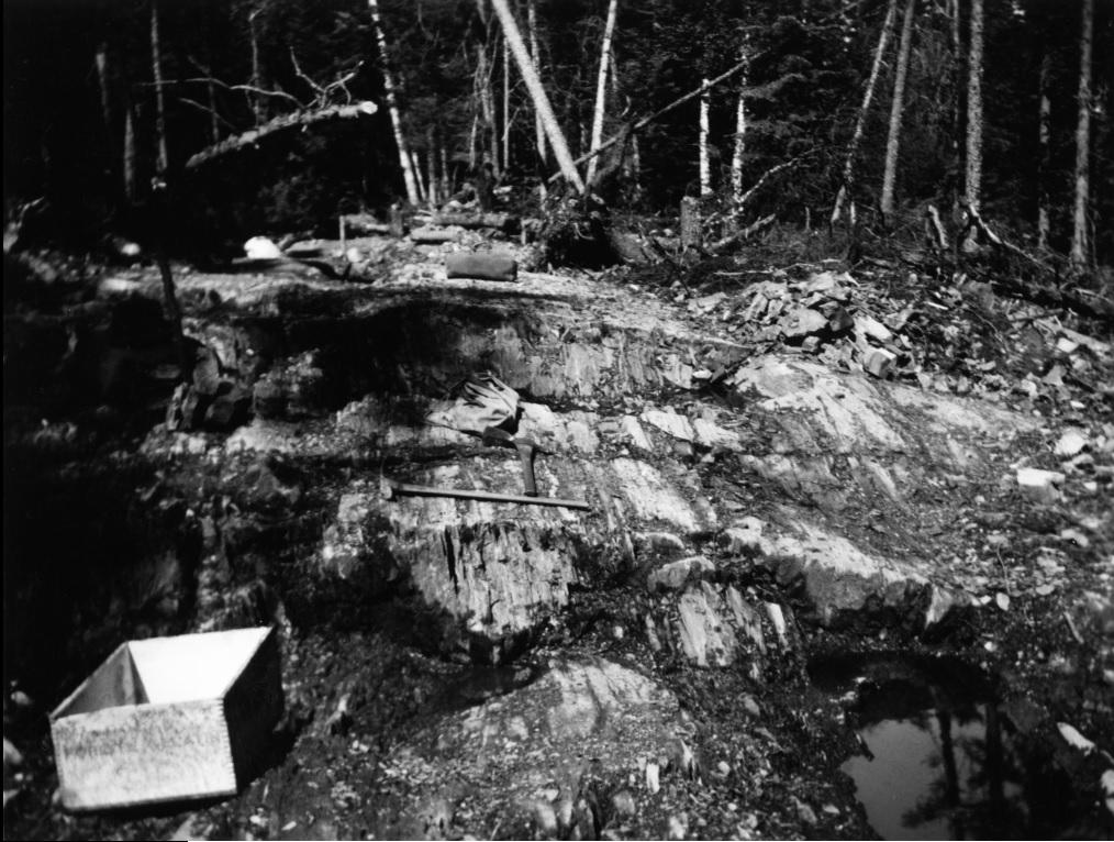 Photo en noir et blanc d'un sol rocheux, ainsi que de deux pioches et de deux boites de bois, avec la forêt en arrière-plan.