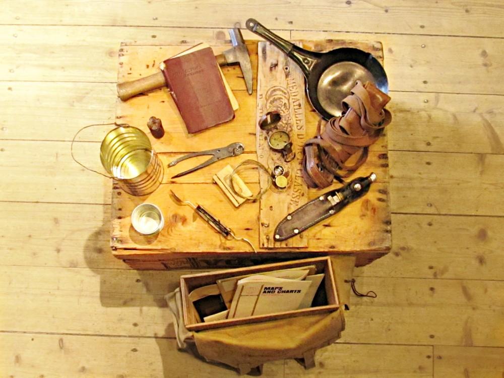 Photographie couleur d'une quinzaine d'artefacts reliés à la prospection étalée sur une boite de bois et d'un sac à dos en toile qui contient une structure en bois déposé par terre.