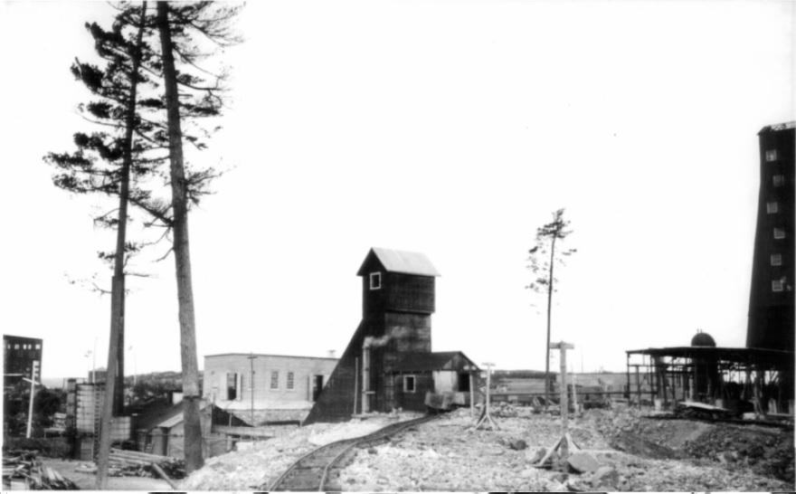 Photographie en noir et blanc des bâtiments miniers avec un chemin de fer rudimentaire et quelques arbres éparpillés.