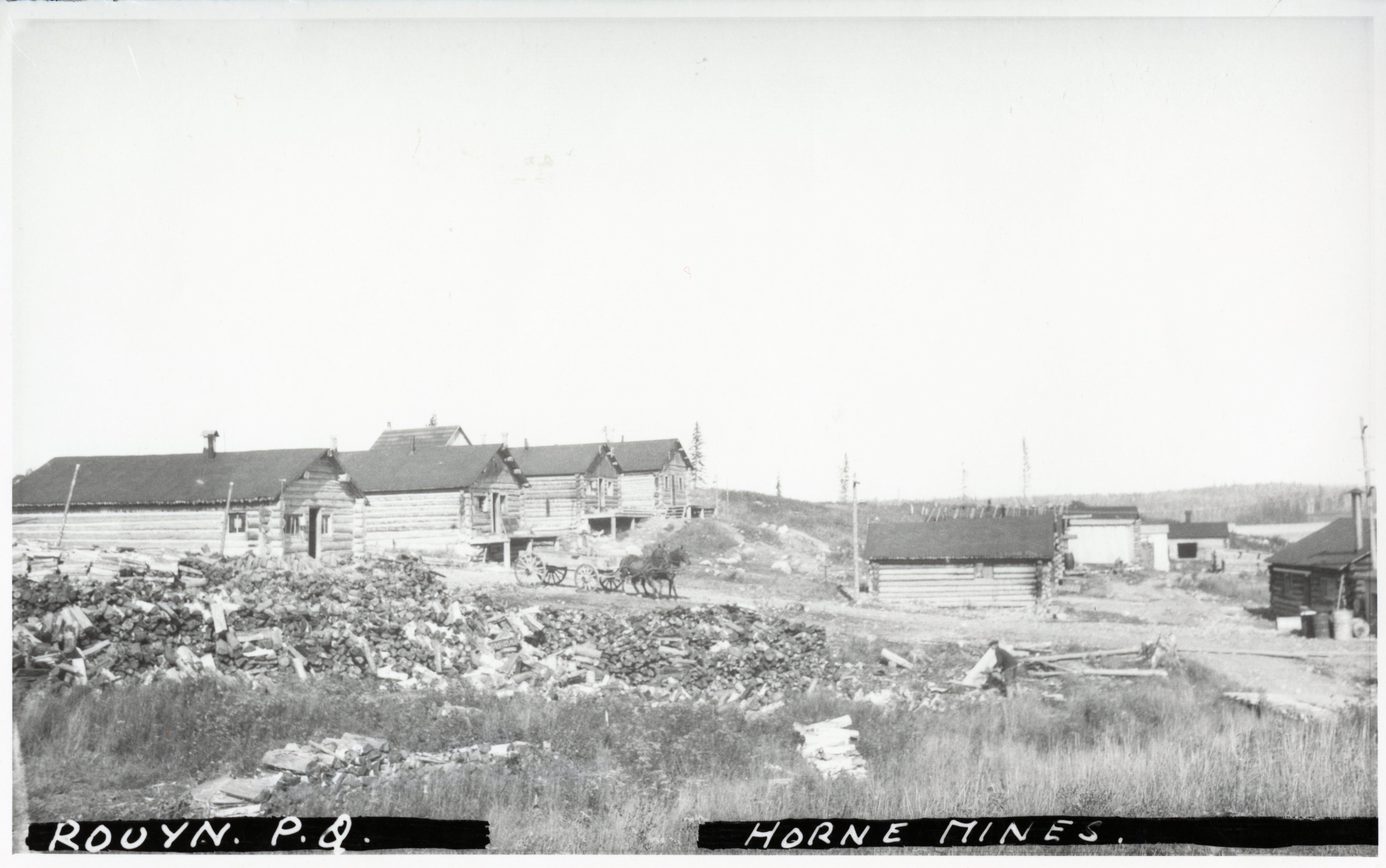 Photographie en noir et blanc de plusieurs cabanes en bois rond, d'une charrette tirée par deux chevaux et de nombreux amoncellements de bûches.