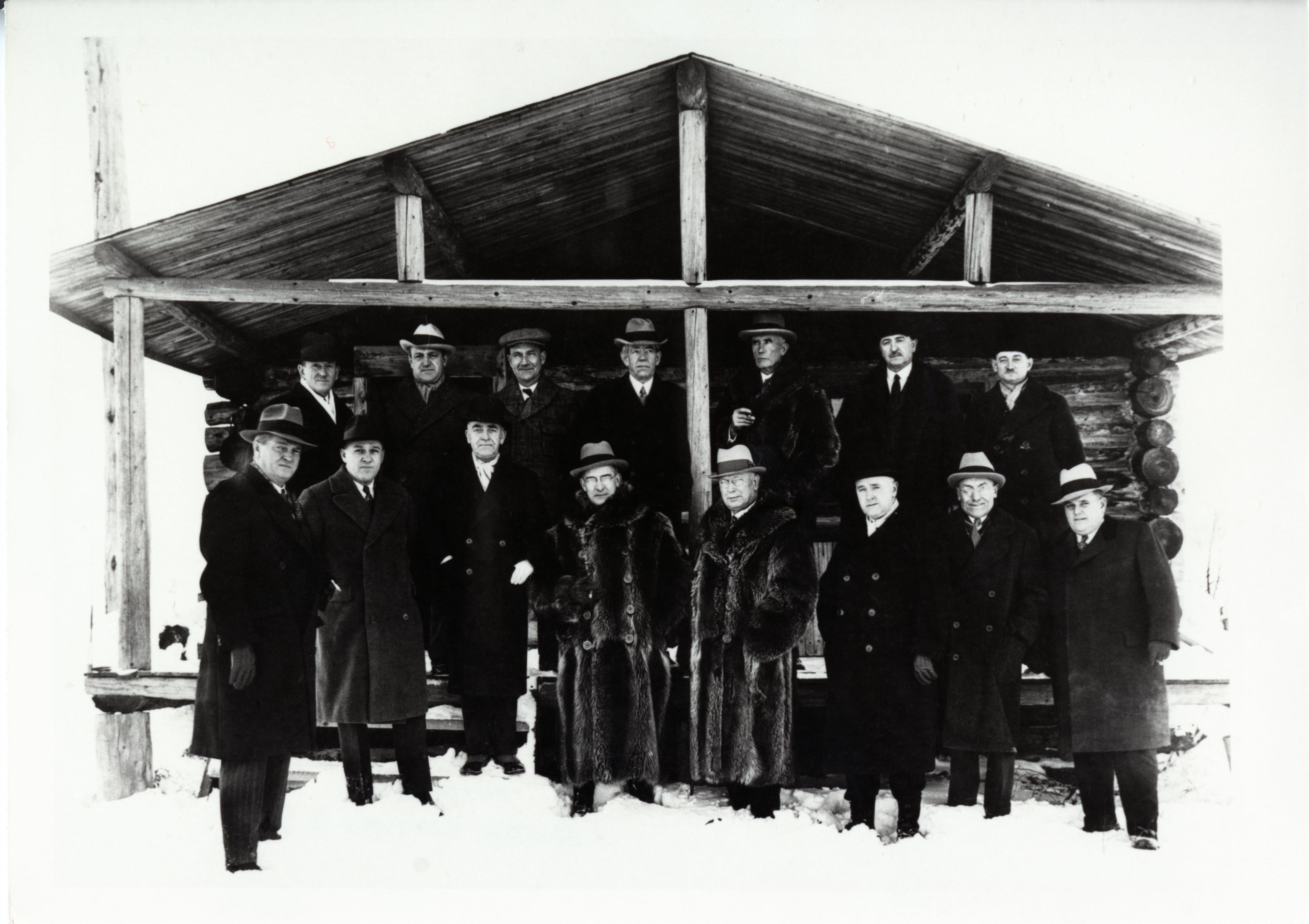 Photographie noir et blanc de quinze hommes en habit chic, dont trois avec des manteaux de fourrure, devant une cabane en bois rond.