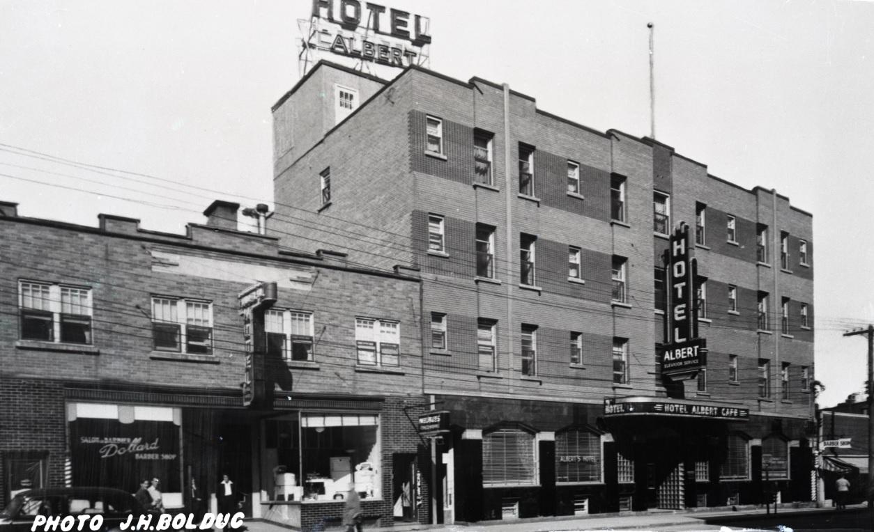 Photographie en noir et blanc d'un bâtiment à quatre étages avec plusieurs enseignes, dont une sur le toit, qui indique Hotel Albert. À gauche, un édifice à deux étages.