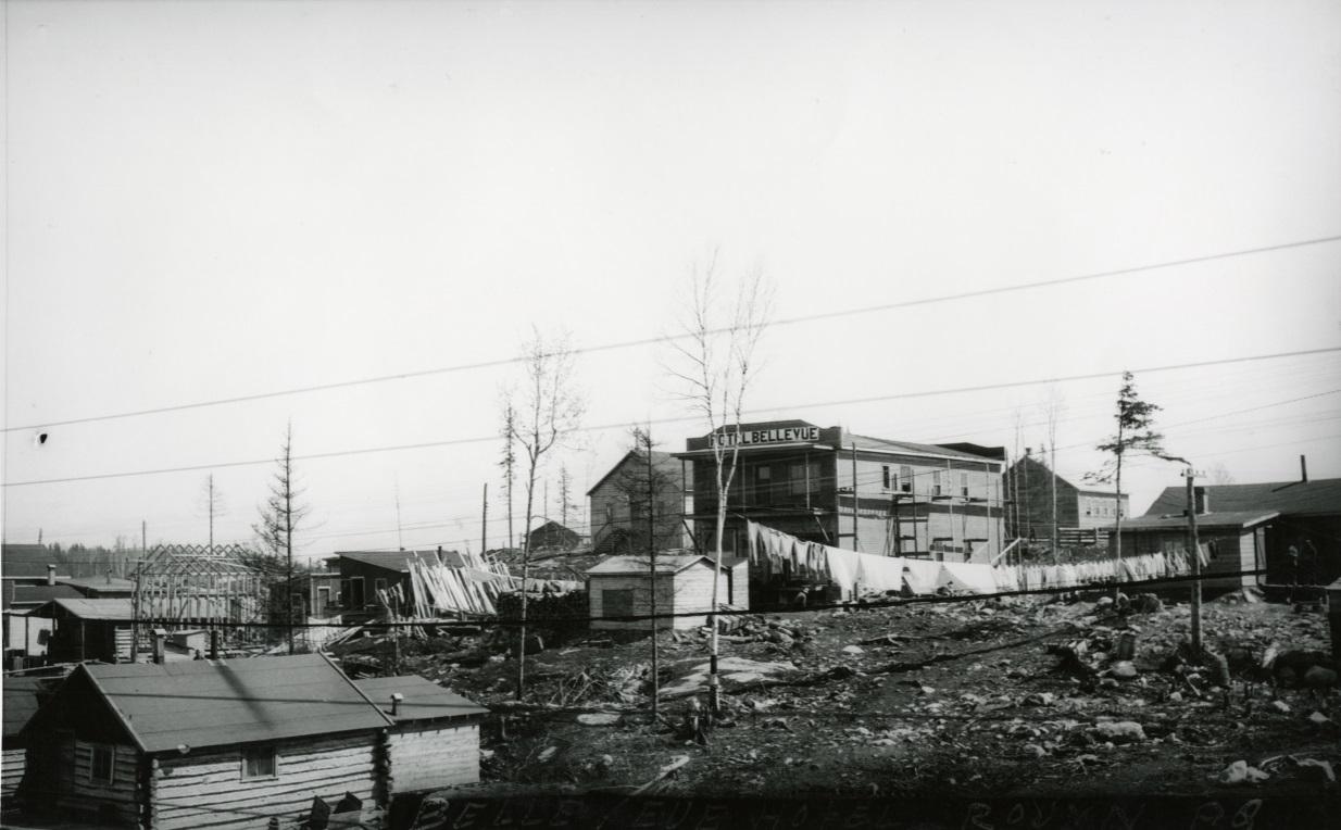 Photographie en noir et blanc de plusieurs bâtiments rudimentaires, en planche ou en bois rond, dont l'un avec l'inscription Hôtel Bellevue sur la façade de style Boomtowns.