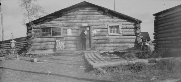 Photographie en noir et blanc d'un bâtiment en bois rond, avec un trottoir de bois menant à l'entrée. À l'avant, un homme en habit et une pompe à essence.