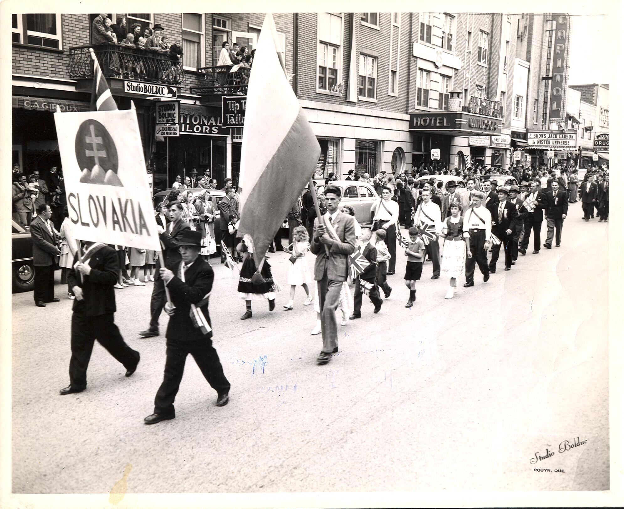 Photographie en noir et blanc d'environ vingt-cinq personnes qui défilent, devant une foule sur le trottoir de la rue Principale, avec une affiche portant l'inscription Slovakia surmonté du blason national et d'un drapeau de la Slovaquie.