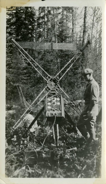 Photographie en noir et blanc d'un homme en habit de travail qui se tient debout à côté  du panneau de commande d'un appareil composé de quatre antennes disposé en croix. En arrière-plan, la forêt.