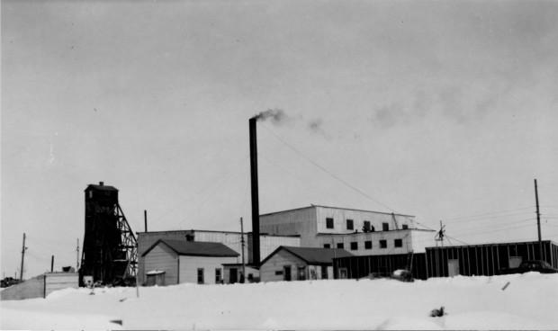 Photographie en noir et blanc de plusieurs bâtiments miniers en planche, dont un chevalement et une cheminée, avec de la neige au sol.