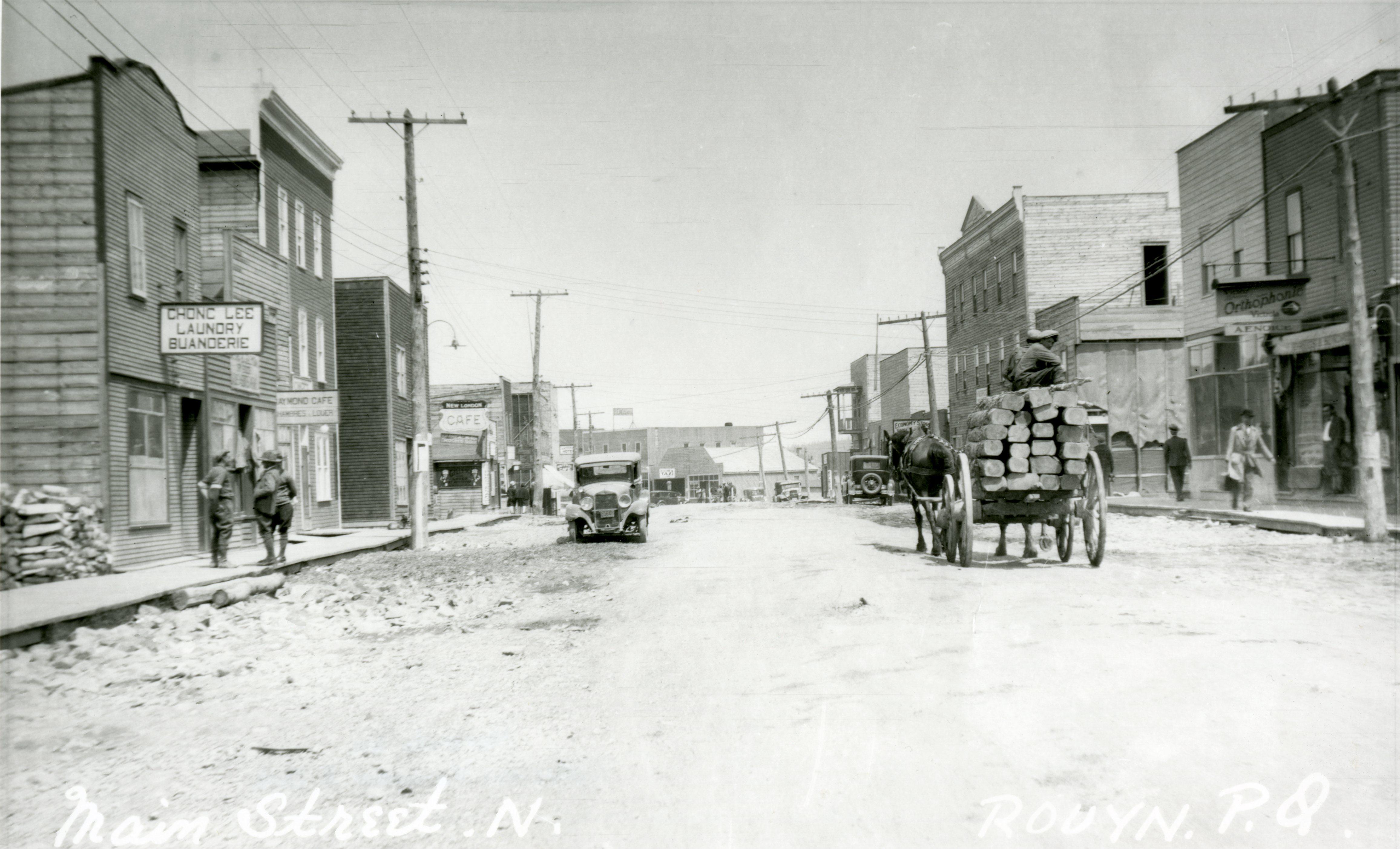 Photographie en noir et blanc d'une rue en gravier sur laquelle une voiture et une carriole tirée par deux chevaux circulent. Des gens marchent sur les trottoirs de bois. Les édifices ont des façades de type Boom-Towns. Une affiche à gauche indique Chong Lee Laundry Buanderie.