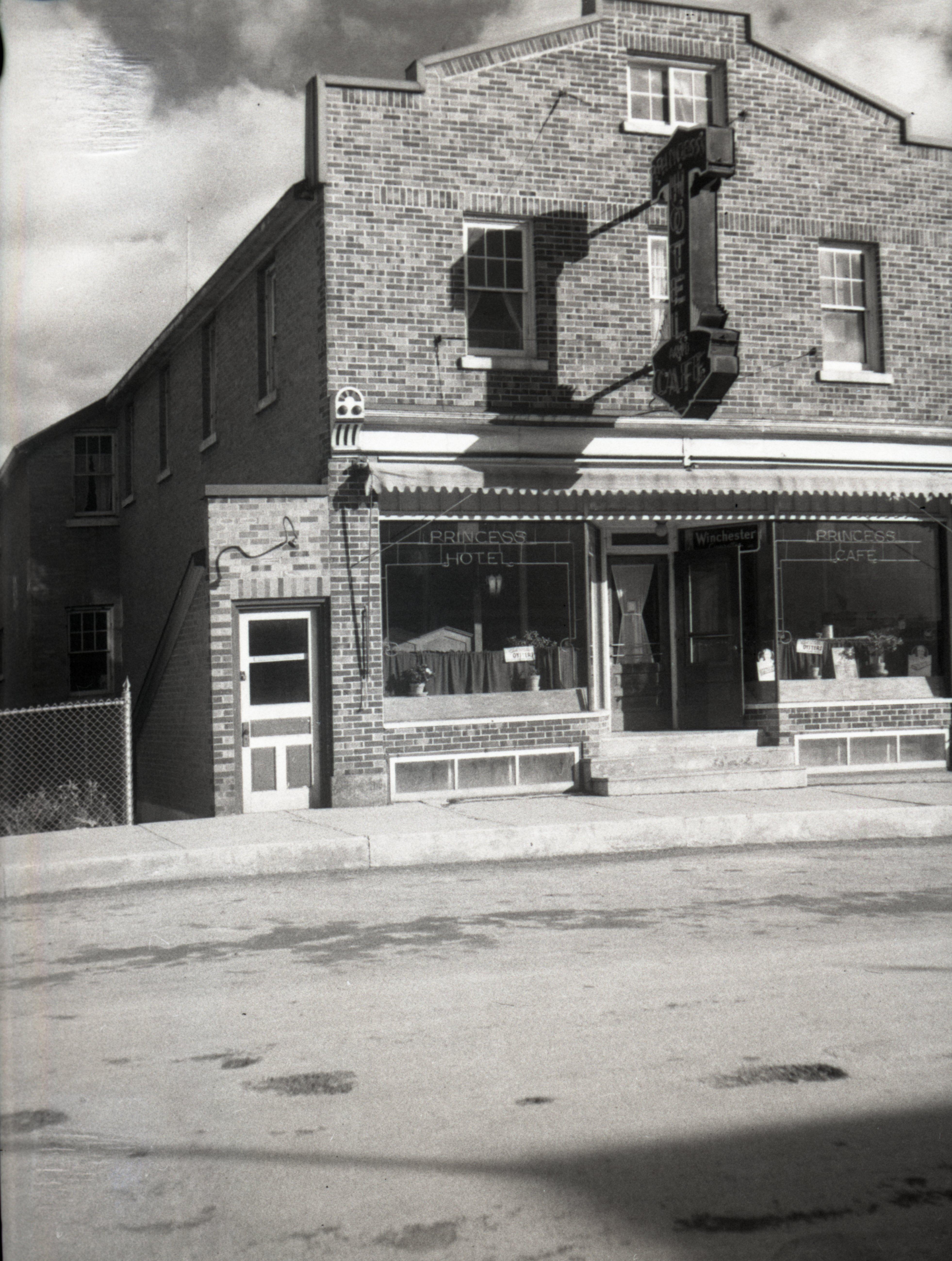 Photographie en noir et blanc d'un édifice de trois étages en brique.En plein milieu de l'édifice, une affiche annonce le Princess Hotel et àgauche, une porte semble menée au sous-sol.