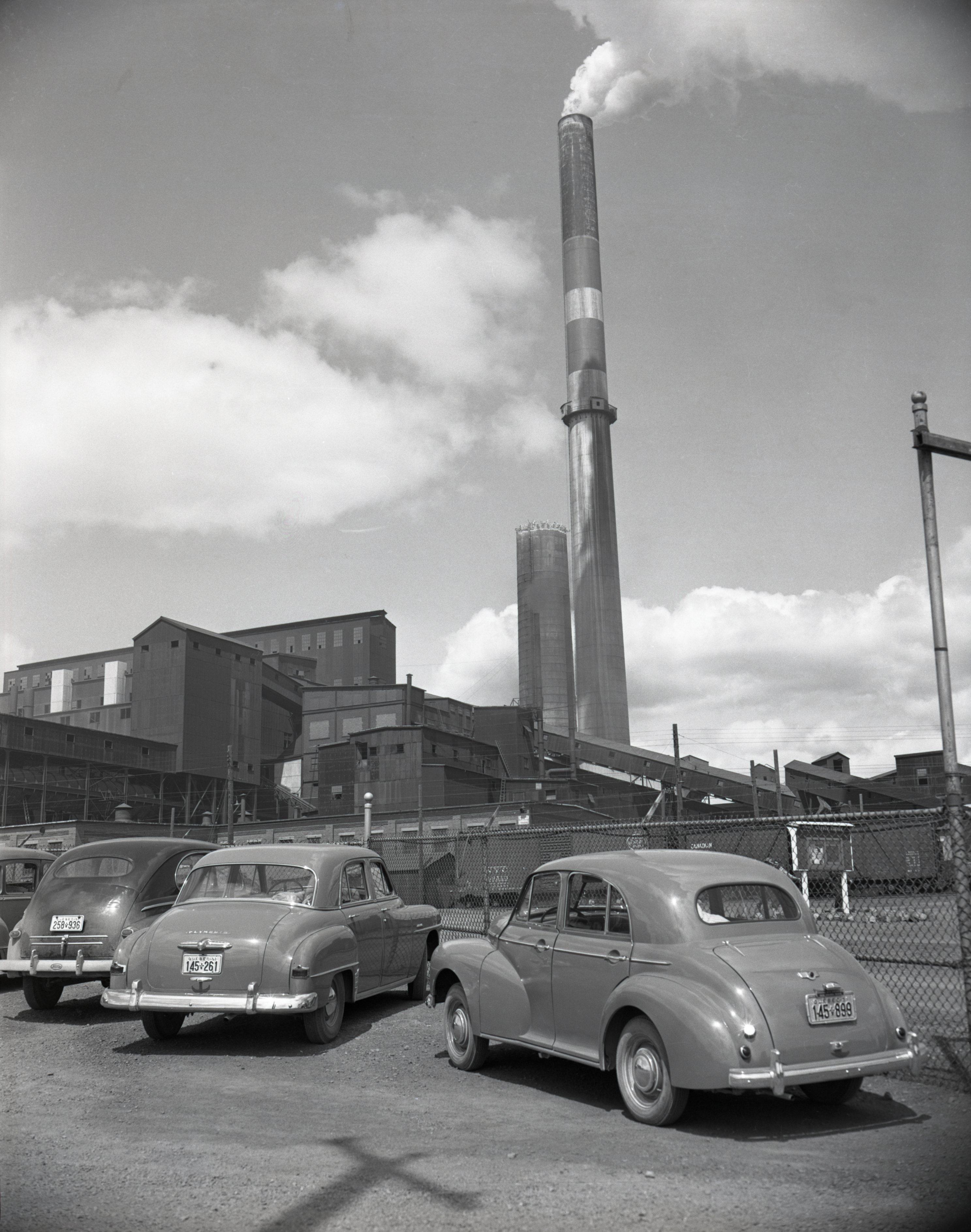 Photographie en noir et blanc  de trois vieilles voitures stationnées devant la clôture de la mine Horne. En arrière-plan, la fonderie ainsi qu'une cheminée qui émet de la fumée.