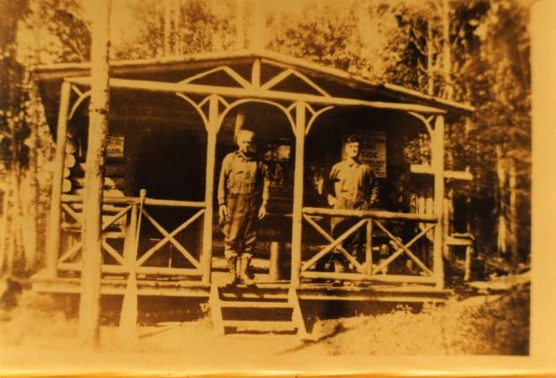 Photographie de couleur sépia de deux hommes debout sur la galerie d'une cabane en bois rond avec la forêt en arrière-plan.