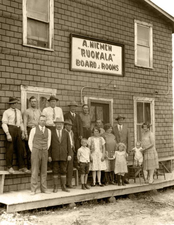 Photographie noir et blanc de seize personnes, dont plusieurs femmes et enfants, devant un bâtiment dont une enseigne indique  A. Niemen Ruokala Board & Rooms.