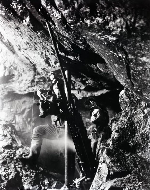 Photographie noir et blanc de deux mineurs qui opèrent une foreuses fixée au sol et au plafond avec des tiges de métal. Ils ont des bottes de caoutchous et un casque avec lumière.