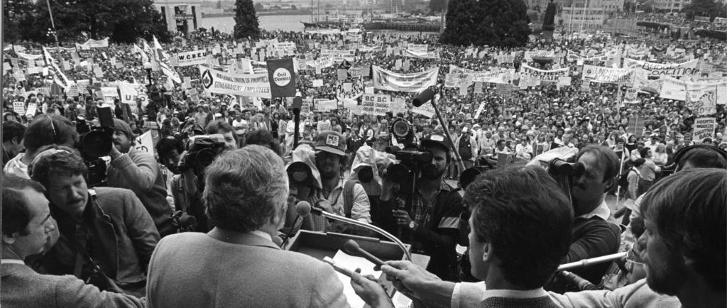 Un homme, prenant la parole devant un podium, fait face à une foule nombreuse sur la pelouse du C.-B. corps législatif. Des journalistes sont rassemblés, tenant des microphones et des caméras vers le podium. Des bannières organisationnelles et des pancartes de protestation sont visibles dans la foule.