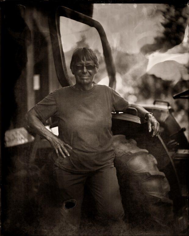 Photographie monochrome aux tons sépia d'une femme debout à côté d'un tracteur, le bras reposant sur une portière ouverte.