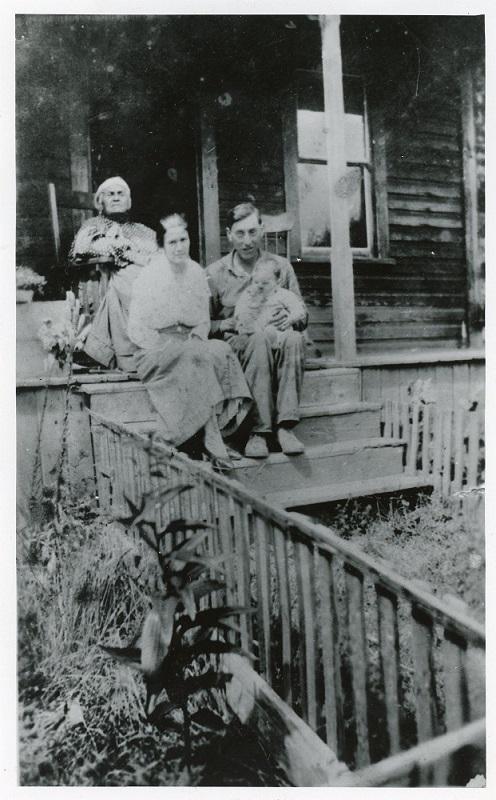 Photographie en noir et blanc d'une femme âgée dans une chaise berceuse en haut des marches d'une véranda; une femme et son mari tenant un bébé sont assis un peu plus bas dans les marches.