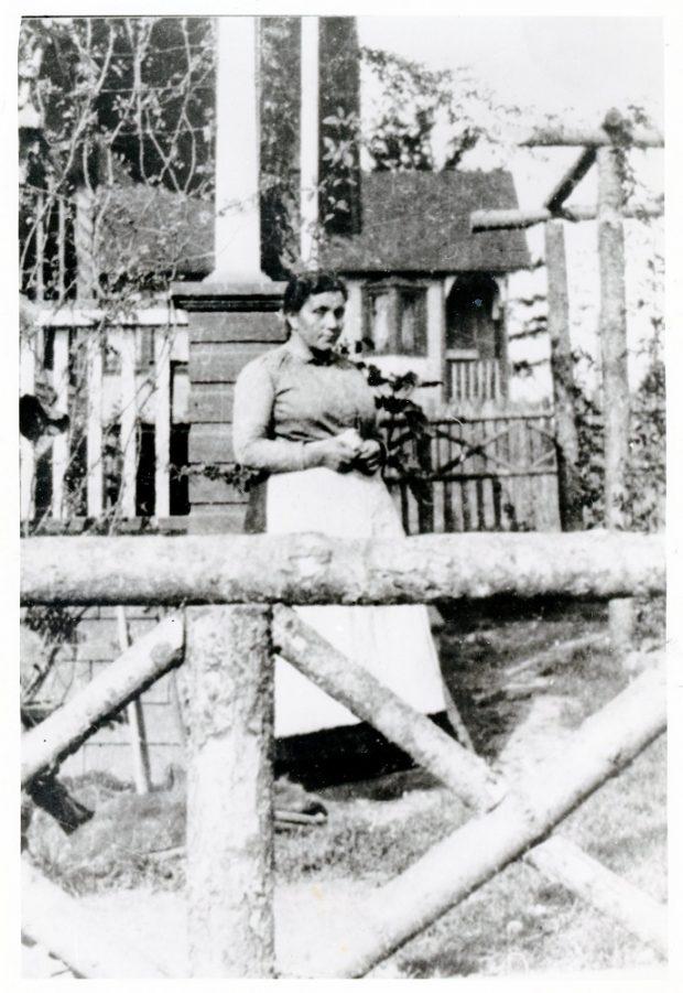 Photographie en noir et blanc d'une femme debout entre un portail de bois et une maison.