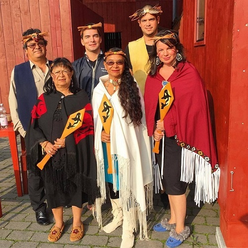 Six personnes — trois hommes et trois femmes — sont debout ensemble, vêtues de la tenue cérémonielle de la Première Nation des T'Sou-ke. À l'avant, trois femmes tiennent des pagaies de bois décorées de l'image d'un épaulard.