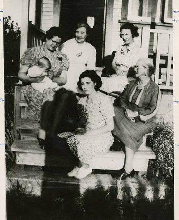 Photographie en noir et blanc de femmes de différentes générations d'une famille, assises ensemble sur des marches de l'entrée d'une maison.