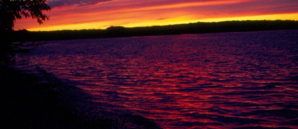 Photographie en couleurs d'un coucher de soleil sur un lac, le ciel prenant des teintes de jaune, d'orange et de mauve.