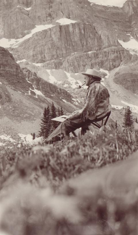 Photo sépia d'un homme portant une veste en daim à franges, un chapeau et fumant la pipe, peignant dans un paysage de montagne.