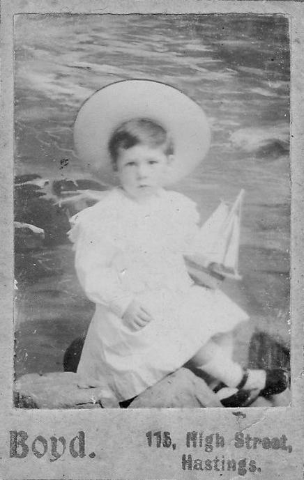 Portrait de studio en noir et blanc d'un jeune garçon tenant un bateau jouet et portant un grand chapeau et une robe blanche.