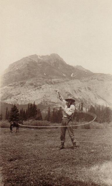 Photo sépia d'un homme en chapeau avec un lasso devant une montagne et un cheval au loin.
