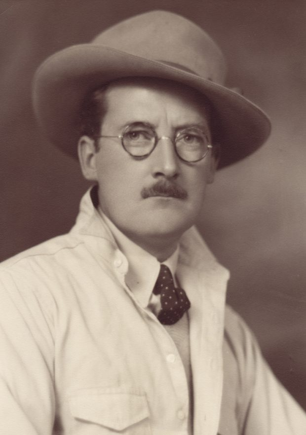 Portrait de studio sépia d'un homme moustachu portant des lunettes, un feutre, une cravate et une veste de couleur claire.