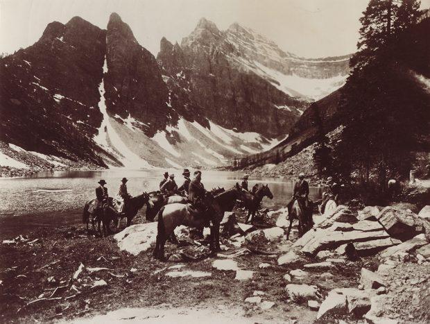 Photo sépia d'un groupe de personnes à cheval au bord d'un lac dans un paysage de montagne.