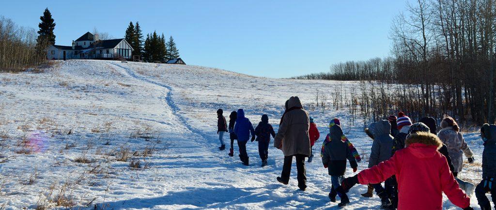 Photo couleur d'une file d'enfants marchant l'un derrière l'autre sur une colline dans un paysage hivernal vers une maison à colombages.