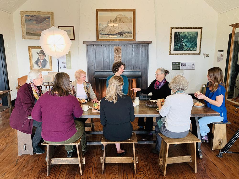 Photo couleur d'un groupe de femmes partageant un repas autour de la table; dessins sur les murs en arrière-plan.