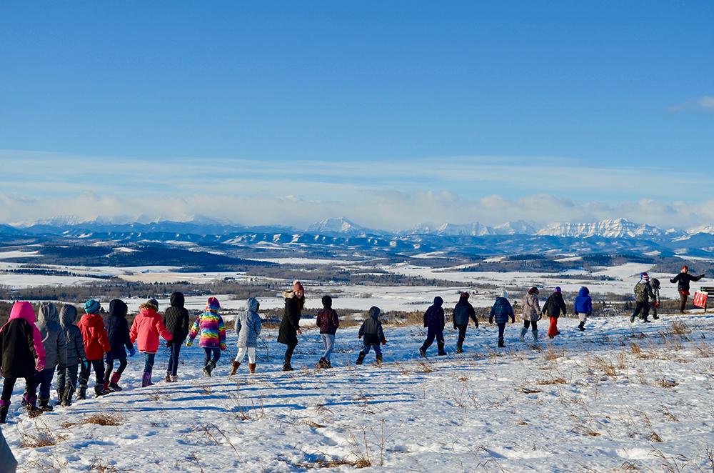 Photo couleur d'une file d'enfants marchant l'un derrière l'autre devant un panorama hivernal de montagnes dans le lointain.