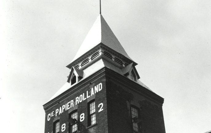 Photographie noir et blanc illustrant une tour reliée à une bâtisse.