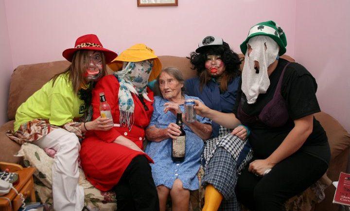 Quatre mummers prennent un verre de rhum assis avec une vieille dame sur un canapé plein à craquer